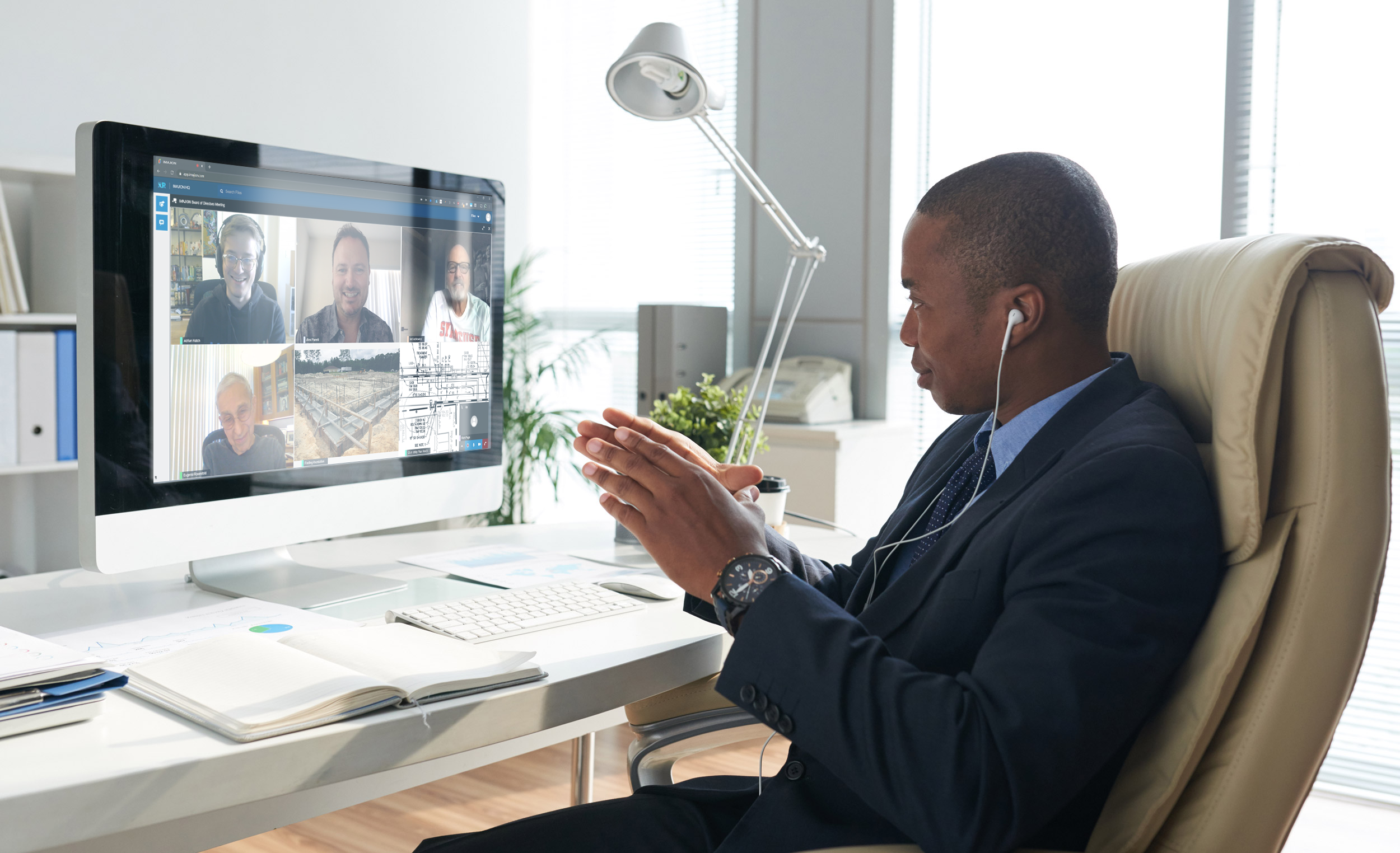 A man attending a video conference at a computer